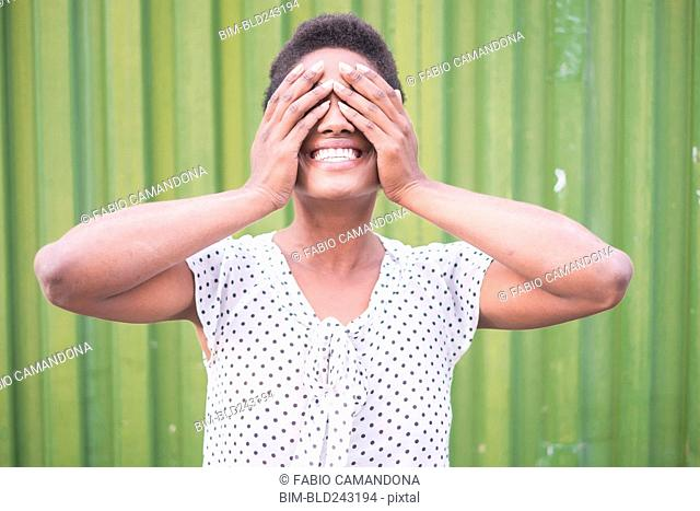 Smiling African American woman covering eyes