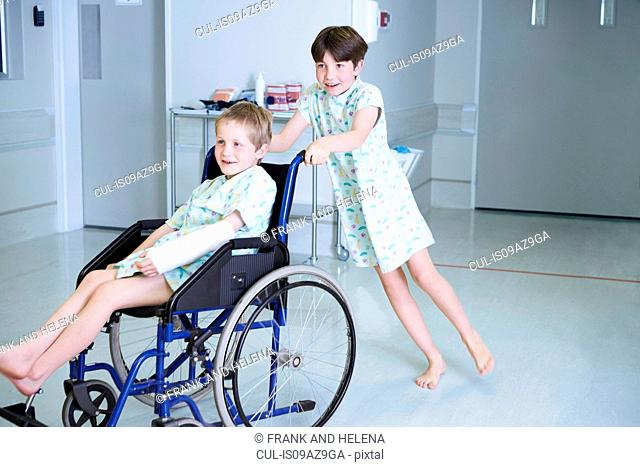 Boy patients pushing friend in wheelchair on hospital children's ward