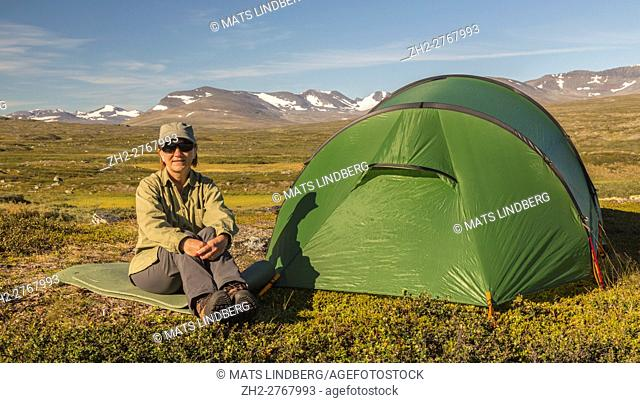 Woman hiking sitting outside the tent, mountains with snow in background, Kiruna, Swedish Lapland, Sweden