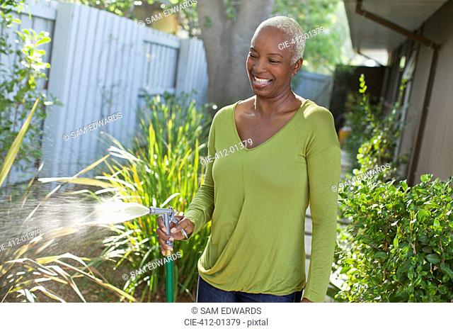Older woman watering plants on beach