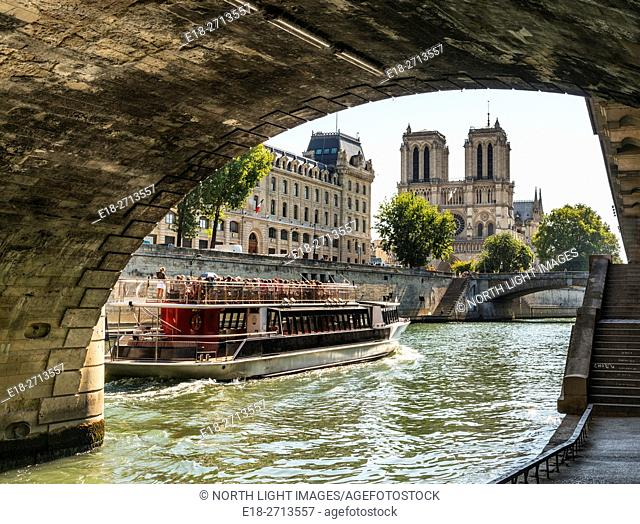 Notre Dame Cathedral viewed from the River Seine under the Petite Ponte bridge, Paris, France