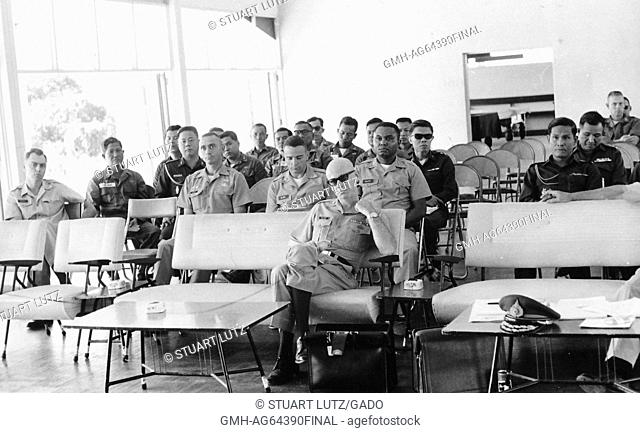 Lieutenant AL Walker sitting in a room with other American and Vietnamese officers, all facing forward, Manhan, Vietnam, 1964
