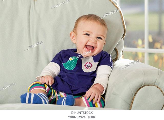 Close-up of a laughing baby on couch