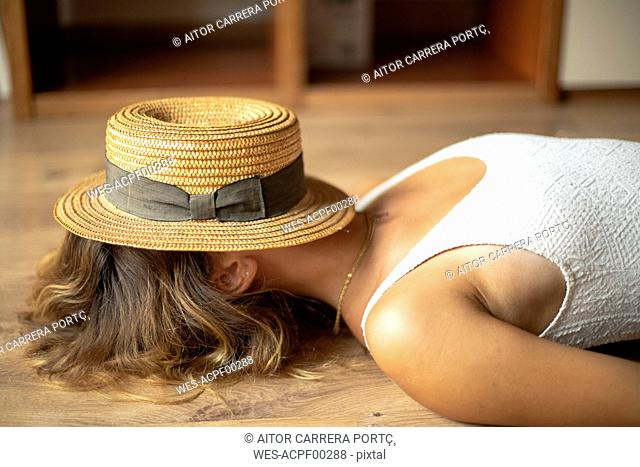 Unrecognisable young woman lying on the floor with a straw hat on her head