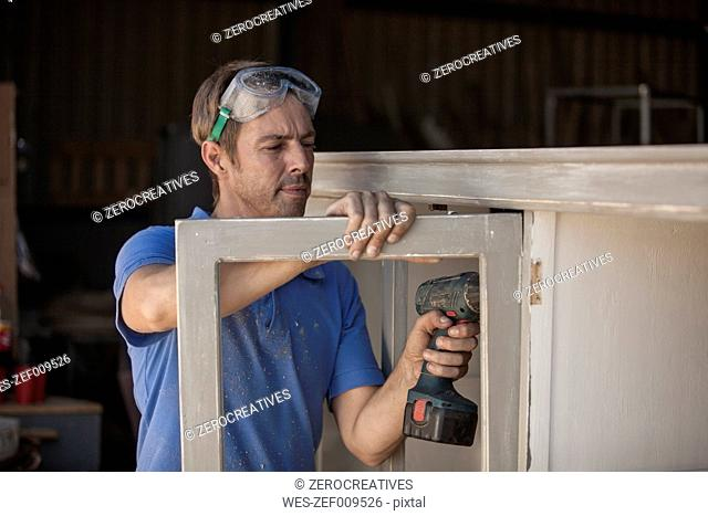 Carpenter using a cordless drill at a cabinet