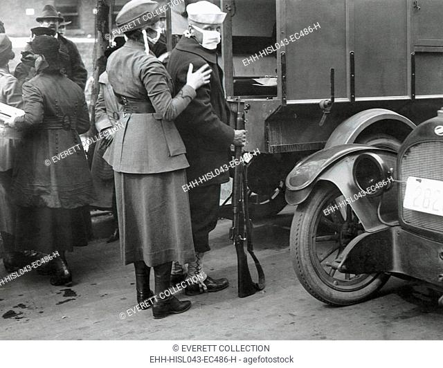 Spanish Flu Epidemic 1918-1919 in America. During the epidemic, a sailor and members of the Womans Motor Corps wear gauze masks while assisting men injured...