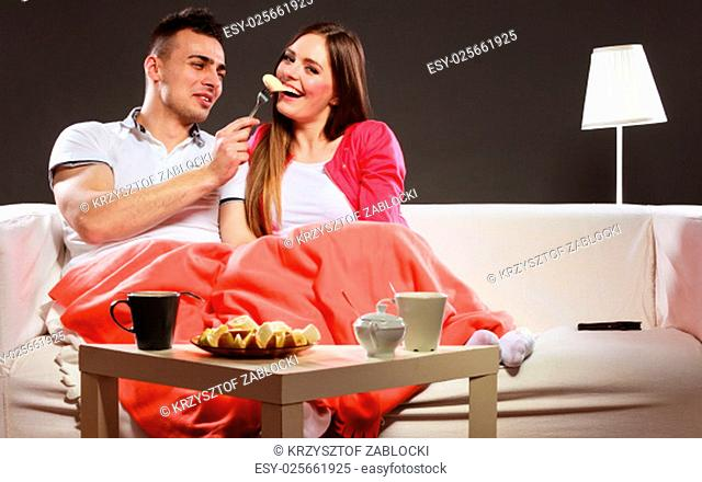 smiling man feeding happy woman with a banana. wife and husband eating fruit. healthy nutrition,dieting and slimming concept