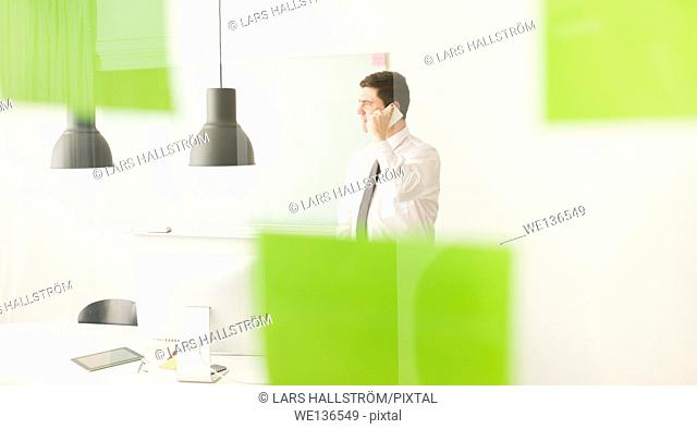 Businessman talking on cell phone behind glass wall with adhesive notes. Conceptual image of business planning