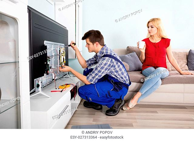 Young Woman Sitting On Couch Looking At Male Technician Fixing Television At Home