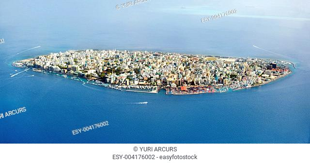 Aerial view of a large island with densely packed buildings and houses as small boats come and go - Maldives