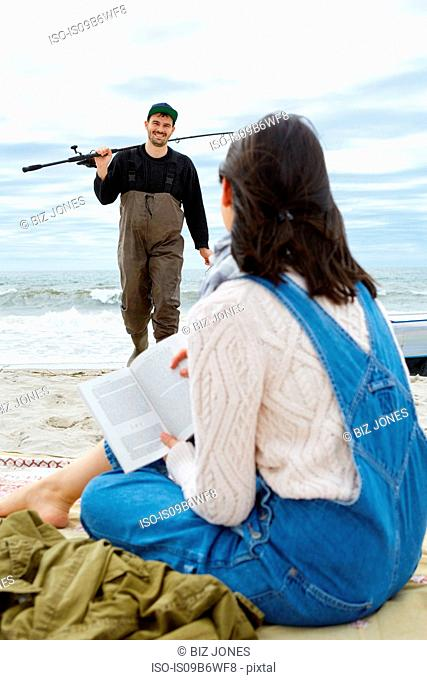 Young woman looking at sea fishing boyfriend on beach