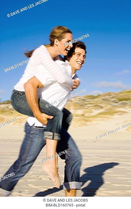 Caucasian man carrying girlfriend piggyback on beach
