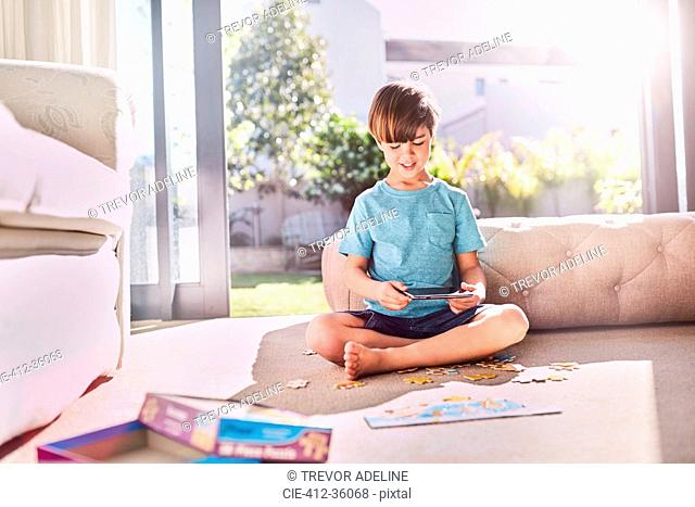 Boy with digital tablet assembling jigsaw puzzle on sunny living room floor