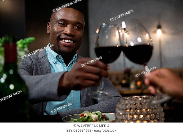 Man toasting red wine while dining