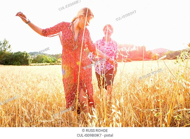 Young woman with boyfriend dancing in wheat field, Majorca, Spain