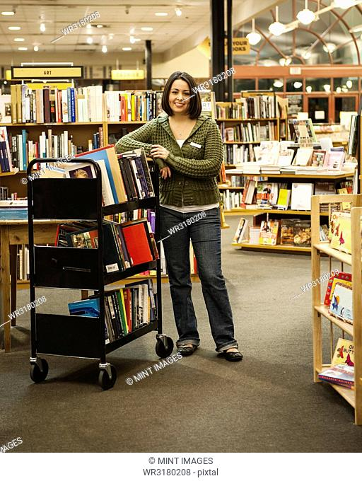 Portrait of a Caucasian female employee standing next to a cart of books in a bookstore