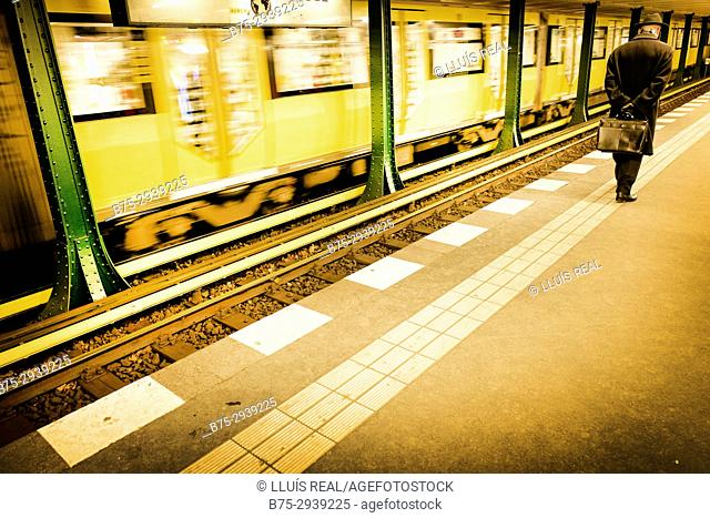 Man and moving train in Wittenbergplatz subway station. Berlin, Germany