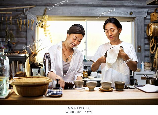 Man and woman standing in a kitchen, cleaning dishes, smiling
