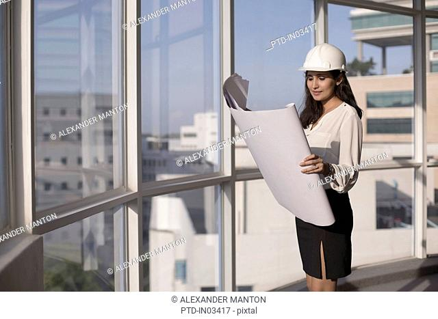 Singapore, Female architect with hardhat looking at building plans