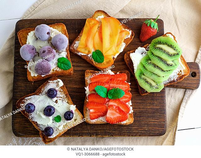 French toasts with soft cheese, strawberries, kiwi, walnuts, cherries and blueberries on a brown wooden board, breakfast