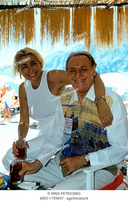 Mara Venier hugging Renzo Arbore. The broadcast presenter Mara Venier and the show man Renzo Arbore drink a cocktail, sitting under a beach umbrella