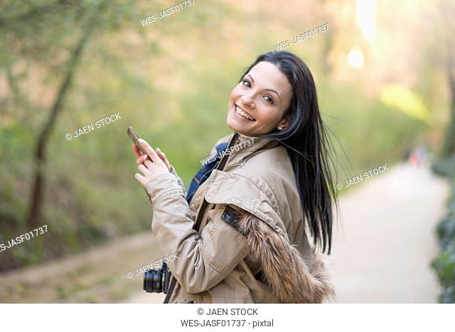 Portrait of smiling young woman with camera and cell phone outdoors