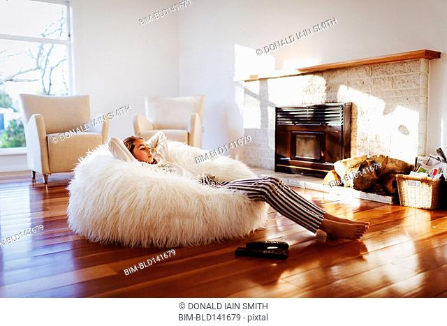 Mixed race girl relaxing in beanbag chair in living room