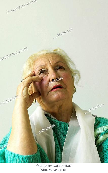 mature woman reflecting and looking up into the sky