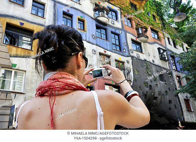Young woman photographing Hundertwasser House, Vienna, Austria