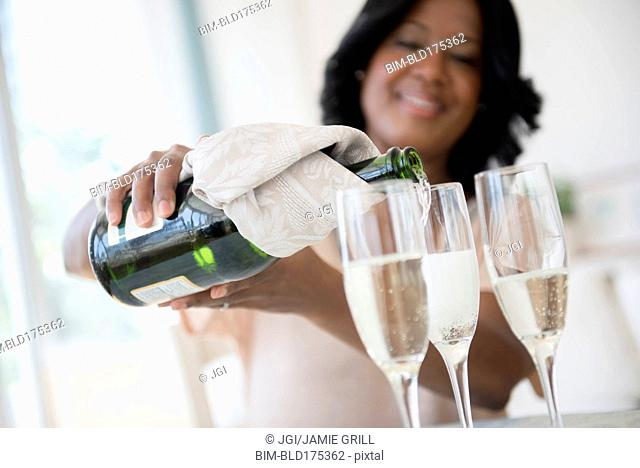 Black woman pouring glasses of champagne