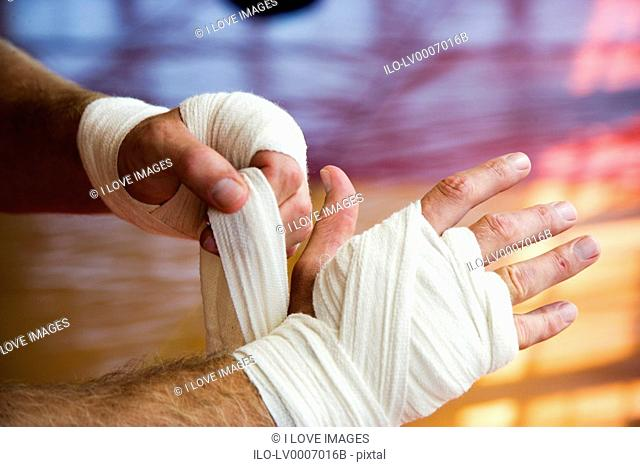 Boxer binding up hands with padding bandages