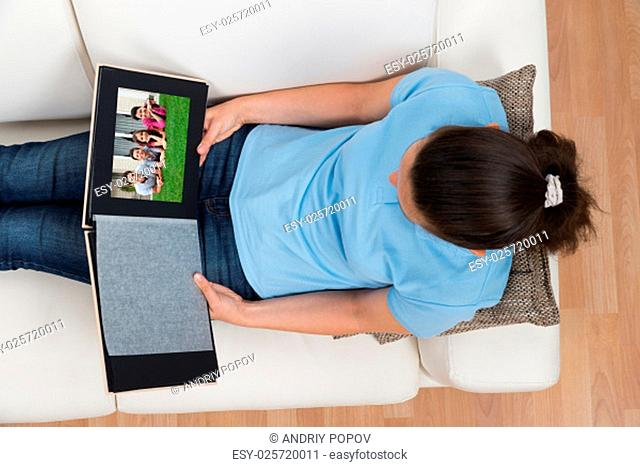 Woman Looking At Family Photo Album While Sitting On Sofa At Home