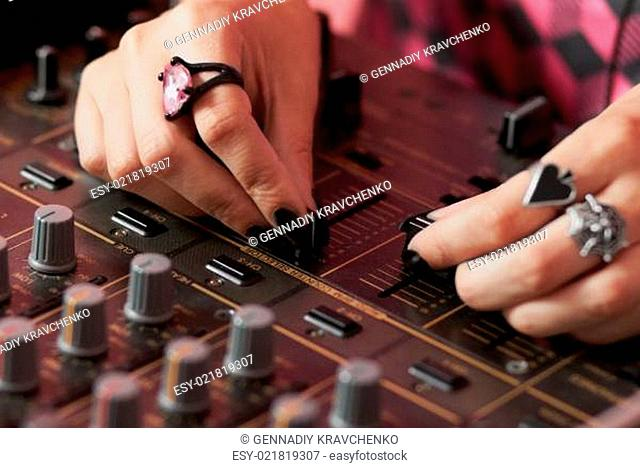 Hands of female DJ mixing music