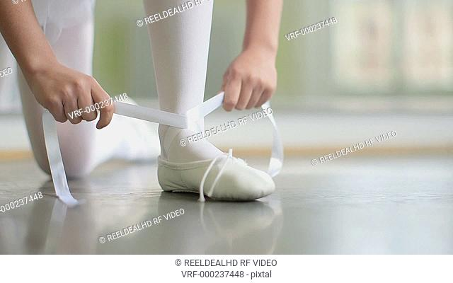 A Young Ballerina wraps the white silk ribbons of her soft top Ballet shoe and ties them up
