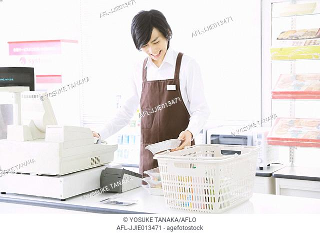 Young Japanese man working at convenience store
