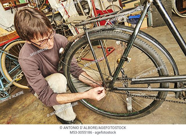 A technician restoring a vintage bicycle