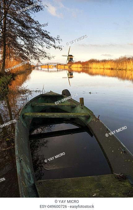 Sunken boat in the canal Ammersche Boezem near Groot-Ammers in the Dutch region Alblasserwaard with the Achterlandse windmill in the background
