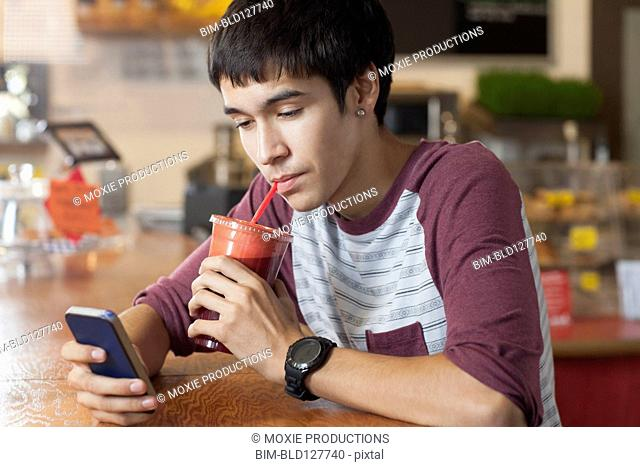 Hispanic teenage boy drinking smoothie in cafe