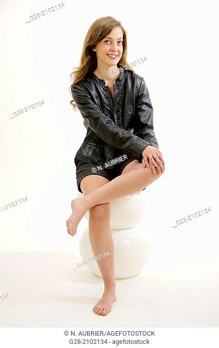 Young sexy woman seating on a white modern plastic stool, dressed in black, shorts and black leather jacket, smiling, legs crossed
