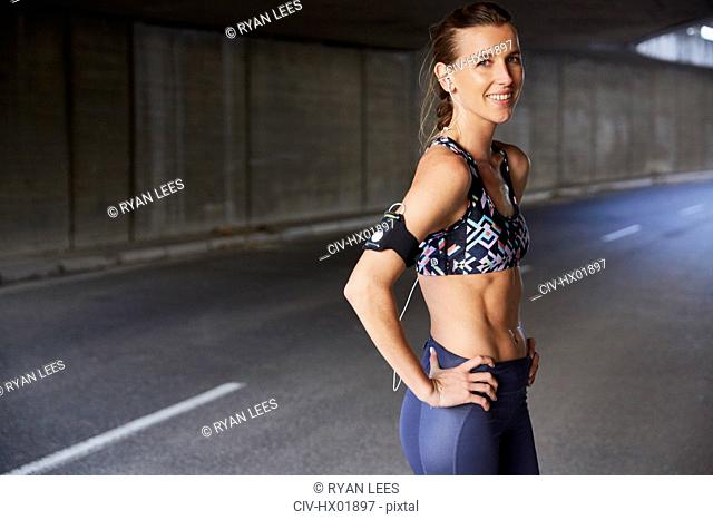 Portrait smiling fit female runner in sports bra with mp3 player armband and headphones in urban tunnel