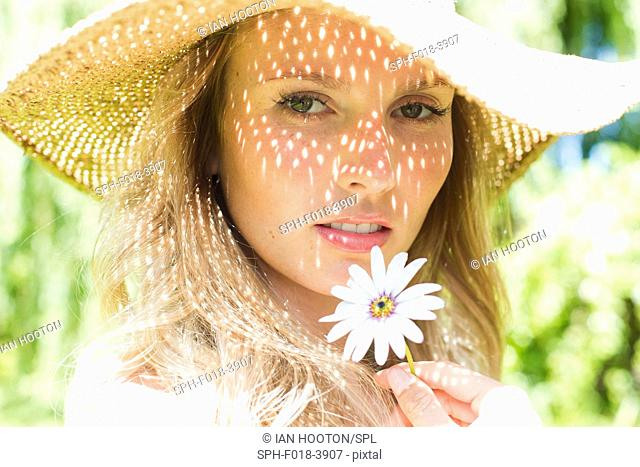 MODEL RELEASED. Young woman wearing sunhat holding daisy