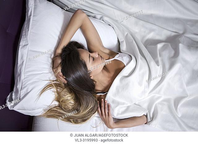 From above shot of tender sensual woman lying on bed with white linen and sleeping