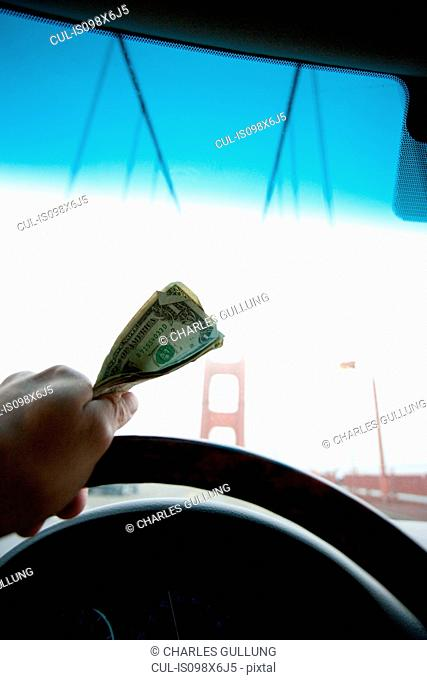 Person holding toll money for Golden Gate Bridge