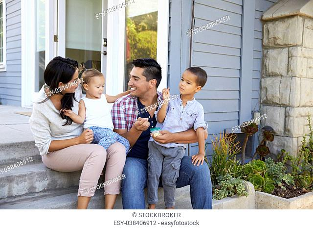 Father Giving Children Candy On Steps Outside Hose