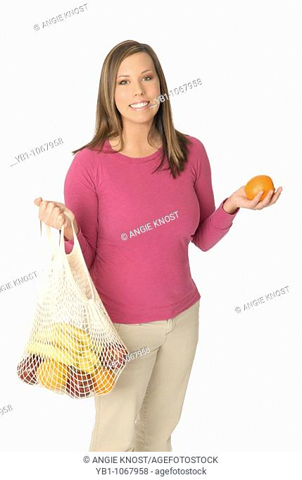 Attractive woman in her 20s with reusable string bag of fruit