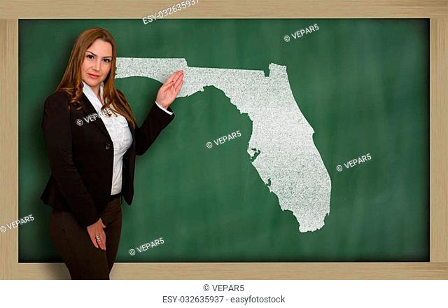 Successful, beautiful and confident young woman showing map of florida on blackboard for presentation, marketing research and tourist advertising