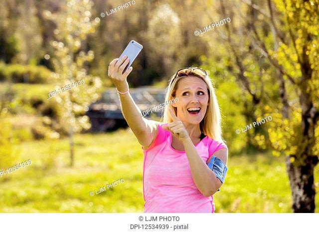 A mature woman wearing active wear and an arm band to hold her smart phone takes a self-portrait before heading out for a run in a city park during the fall...