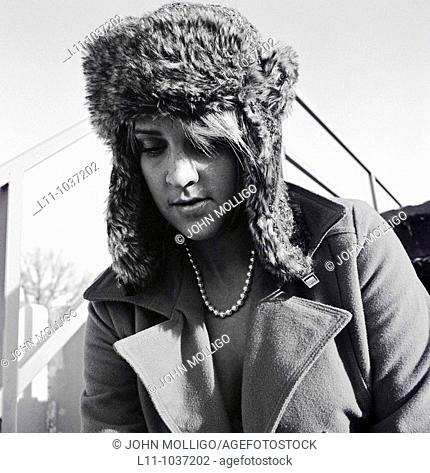 Woman in ushanka and coat, looking down