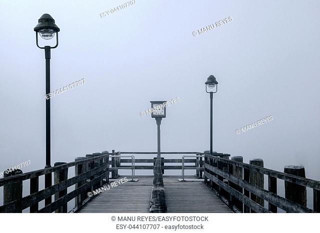 Views of the lonely wooden pier in the fog with two lampposts and old clock on the lake Konigsee in Germany