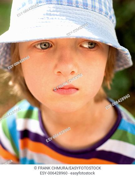 Portrait of a Boy with Blond Hair and Hat Outdoors